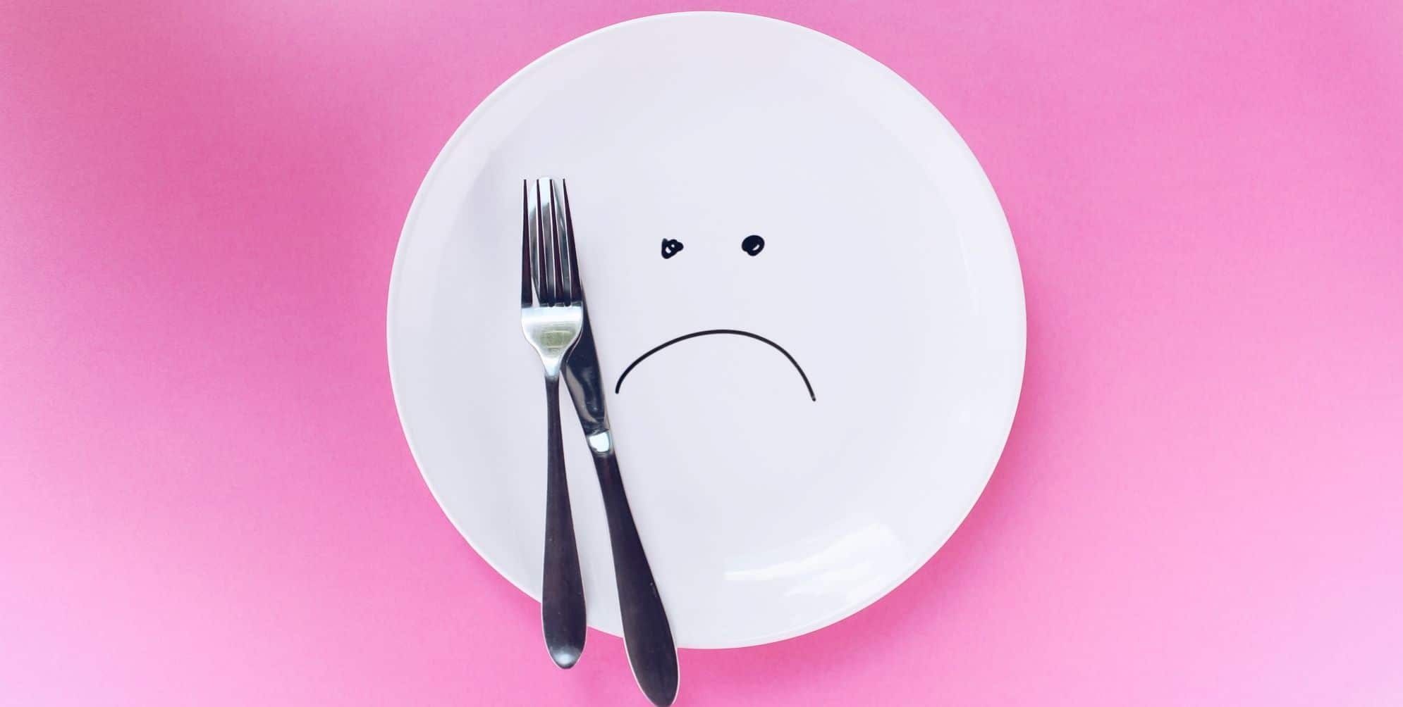 white plate on pink backgorund with knife and fork. Plate has an unhappy face on it :(