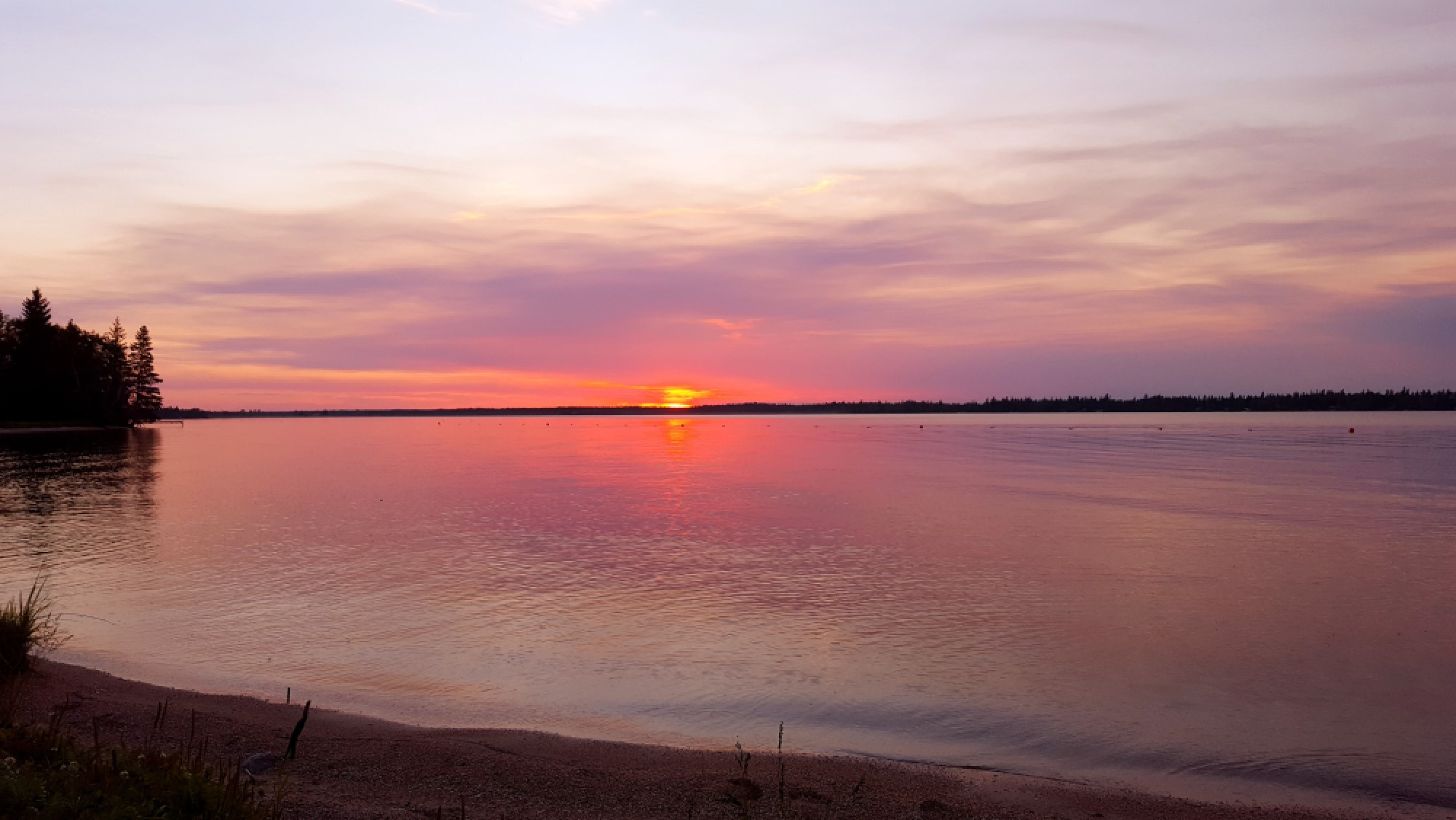 sunset over a lake, red sun, clouds are purple